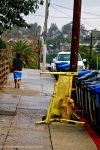 Woman walking down rain drenched Los Angeles residential street.