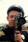 White police officer shoots film of marchers.
